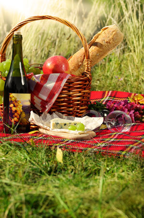 Basket with wine cheese and fruits. Picnic ideas concept photo
