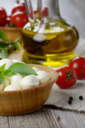 Mozzarella cheese, cherry tomatoes, basil leaves and olive oil - caprese salad ingredients photo