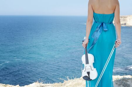 Woman in cyan dress holds violin and bow at sea shore photo