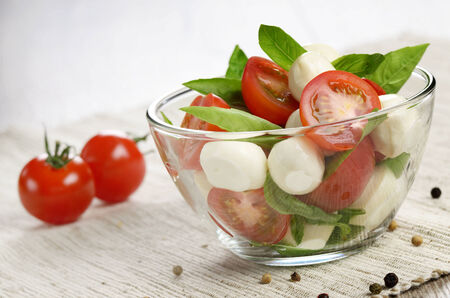 verduras verdes: Ensalada Caprese casera en un taz�n de vidrio con pan italiano