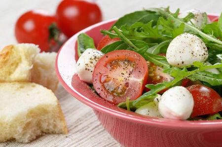Homemade Caprese salad in ceramic bowl with italian bread photo