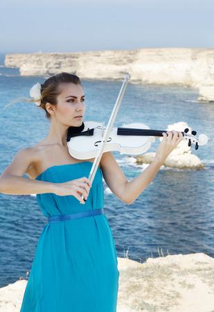 Young beautiful romantic woman cyan dress playing violin at sea shore photo