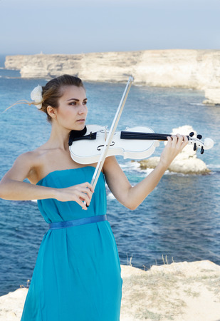 Young beautiful romantic woman cyan dress playing violin at sea shore photo