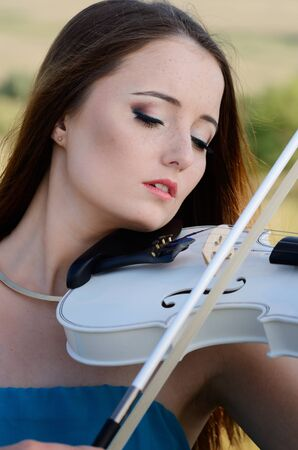 fiddle: Young beautiful romantic woman in dark cyan dress playing music on white fiddle