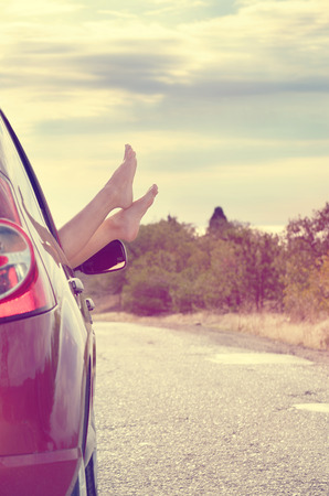 Female bare feet stick out of car window on mountain background. Travel concept.