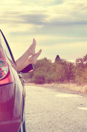 pies bonitos: Pies desnudos femeninos sobresalen de la ventana del coche en el fondo de la monta�a. Concepto del recorrido.