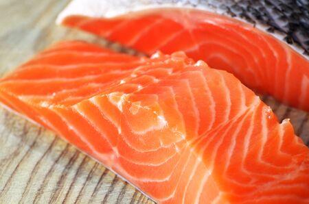 Raw salmon fillet on cutting board photo