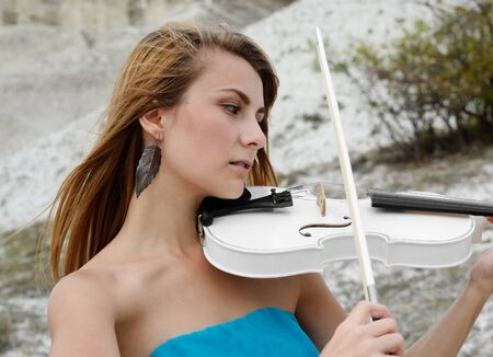fiddle: Young beautiful woman in dark cyan dress playing music on white fiddle Stock Photo