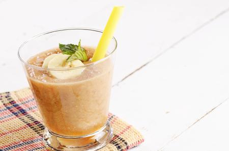 shake: Carrot and banana shake on white table. Smoothie concept
