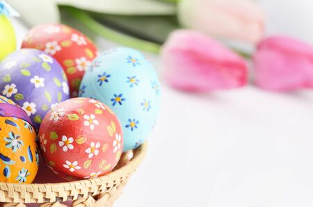 easter flowers: Easter decorations - flowers, basket with painted eggs on white