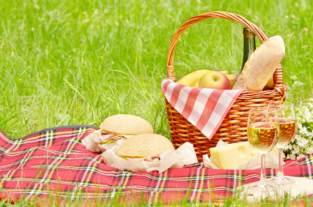 picnic cloth: Picnic basket with apples bread cheese wine and sandwiches Stock Photo
