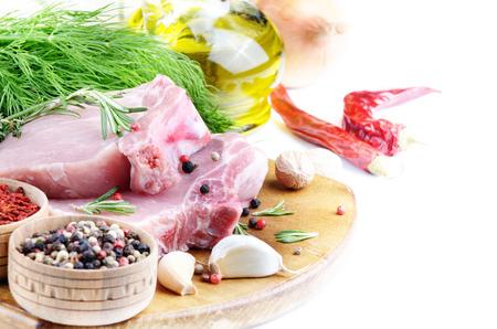 pimenton: chuletas de costilla de cerdo cruda en la tabla de corte con romero, ajo y aceite de chile Foto de archivo