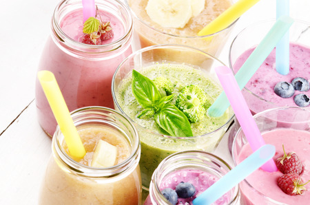 raspberries: Assorted fruit and vegetable shakes on white table. Smoothie concept Stock Photo