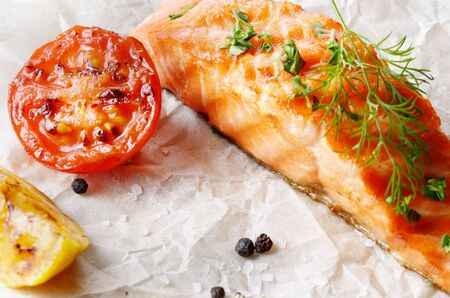 cooked fish: Fried Salmon fillet with lemon tomato and spices rustic serving