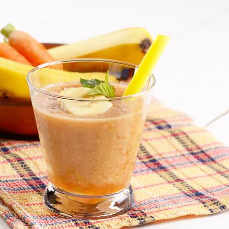 banana: Carrot and banana shake on white table. Smoothie concept