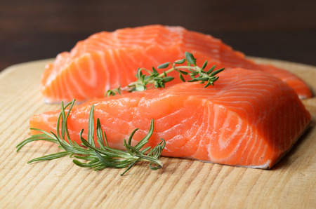 sliced: Raw salmon fillet with rosemary on wooden cutting board