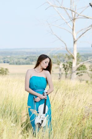 fiddle: Young beautiful woman in dark cyan dress with white fiddle in her hands