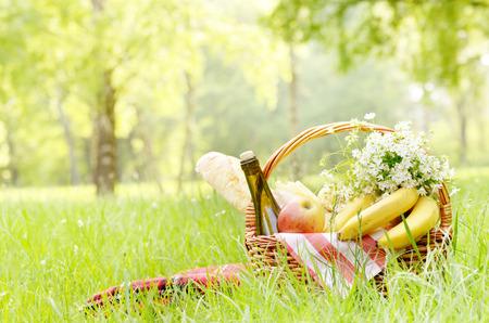 campo de flores: Cesta de picnic con queso manzanas los pl�tanos y el vino en la hierba verde