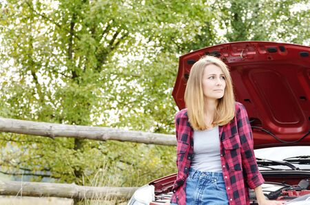 Young sad woman stands near broken car looks under the bonnet Stock Photo
