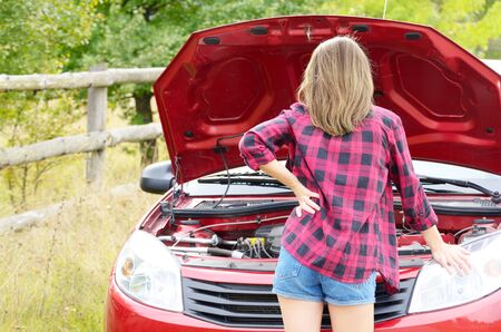 car trouble: Young woman stands near broken car looks under the bonnet