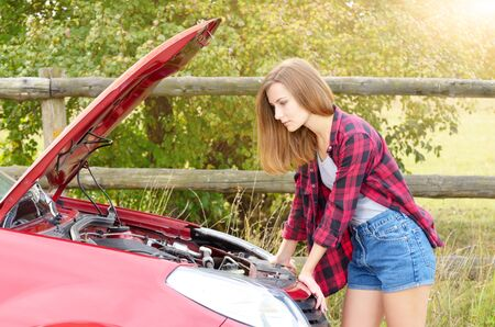 Young woman stands near broken car looks under the bonnet