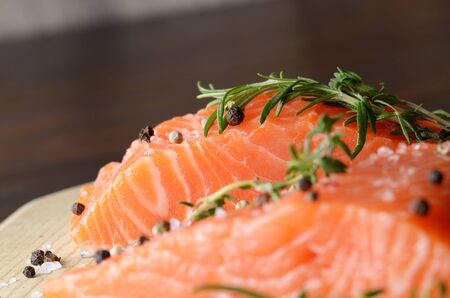 thymus: Raw salmon fillet with rosemary pepper thymus and salt on wooden cutting board