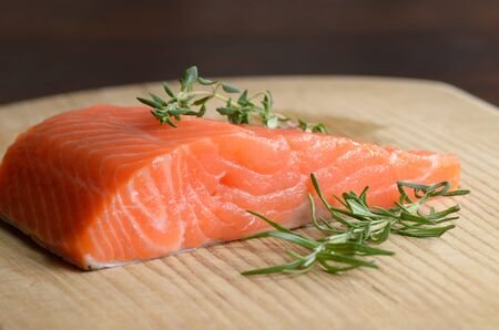 wood board: Raw salmon fillet with rosemary on wooden cutting board