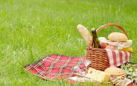 pan y vino: Cesta de picnic con las manzanas pan vino queso y bocadillos Foto de archivo