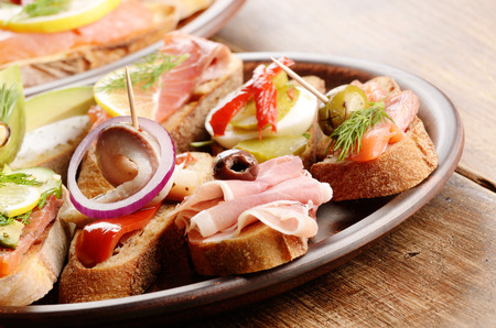 kipper: Open sandwiches with salmon, eggs, mussels, jamon and herring on ceramic plate
