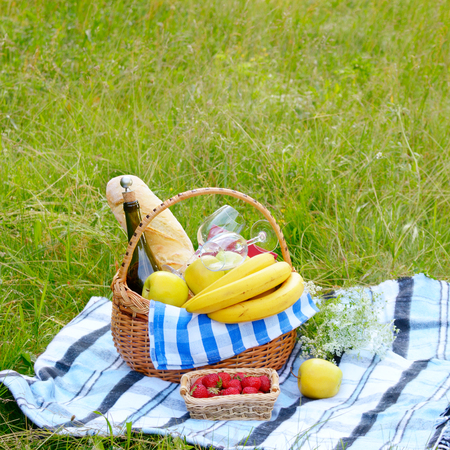 banana bread: Picnic basket with fruits wine and bread on the grass with strawberry aside