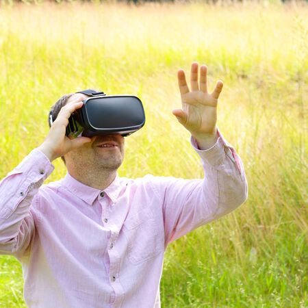 Man wearing virtual reality goggles outdoors First experience in 3d entertainment Stock Photo