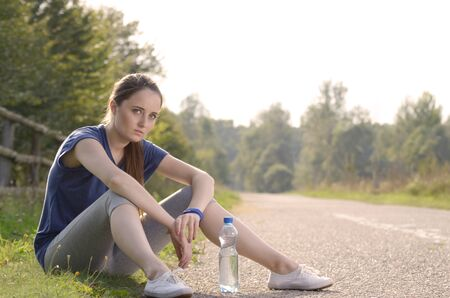 lifestile: Young tired woman having a rest after jogging outdoors summer time. Helathy lifestile concept