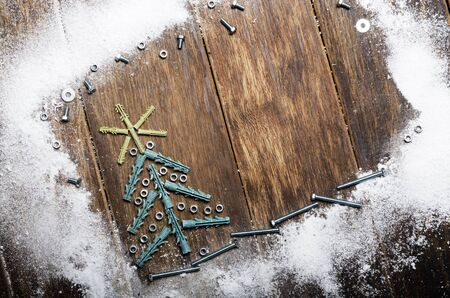 Christmas tree made of wall plugs and nuts background on wooden table