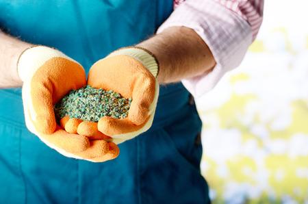 Agricultor mostra fertilizantes em suas mãos weared em luvas Foto de archivo - 89139900