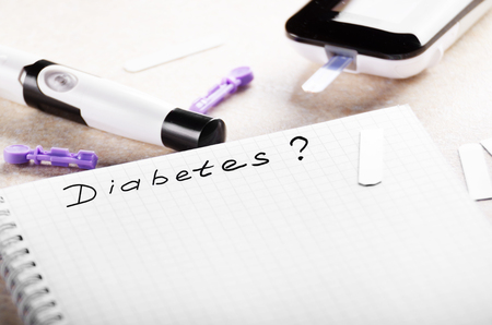 Personal blood glucose meter notebook and lancet on the table Stock Photo