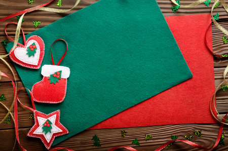 Handmade rustic Christmas tree decorations with red and green felt on wooden table. Space for text