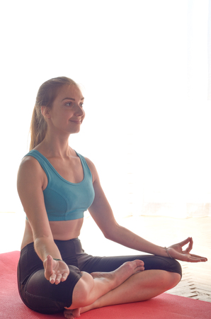 Young happy woman doing yoga sitting meditation at home. Healthy lifestyle concept. Place for text