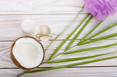 Flat lay Coconut oil in glass bottle bath sponge candle and shell pieces on white wooden table Stockfoto