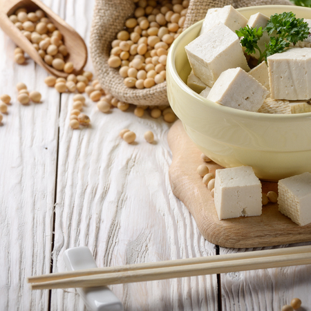 Soy Bean curd tofu in clay bowl and in hemp sack on white wooden kitchen table. Non-dairy alternative substitute for cheese. Place for text Banco de Imagens