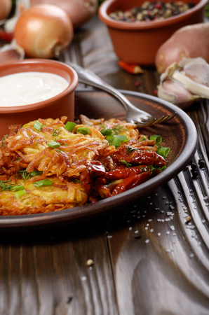Homemade tasty potato pancakes in clay dish with sun-dried tomatoes and sour cream Stock Photo