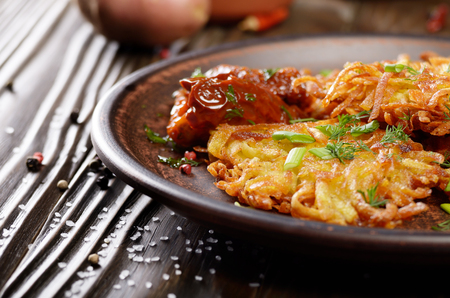 Closeup view at Homemade tasty potato pancakes in clay dish with sun-dried tomatoes Stock Photo