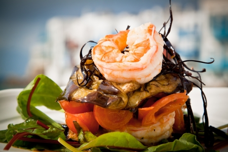 Delicious prawn starter with salad, aubergine and tomato