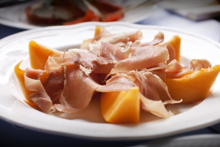 A mouth-watering plate of ham and melon  typical summer meal  Focus on the ham Stock Photo - 13797021