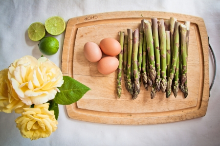 Ingredients for an asparagus salad on a chopping board  asparagi, eggs, lime and yellow roses  photo