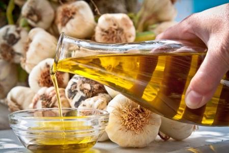 aceite de cocina: Mano vertiendo el aceite extra virgen de oliva en una bwol con ajo fresco en el fondo