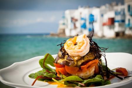 Garnalen starter met aubergine, tomaat en sla bij de zee in Mykonos, Griekenland