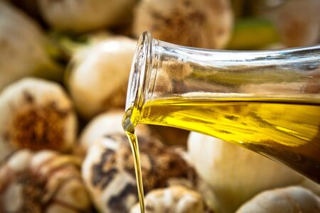Close-up on pouring extra-virgin olive oil with fresh garlic in the background Stock Photo - 13797090