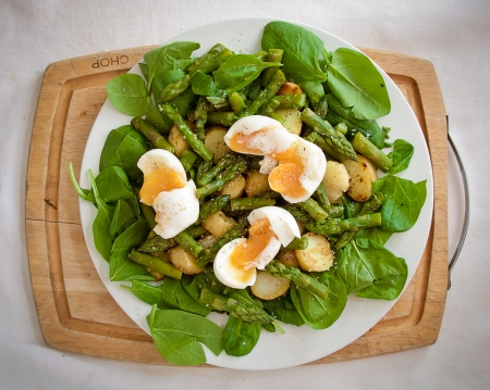 Asparagus salad with spinach, potatoes and soft-boiled eggs on a chopping board photo