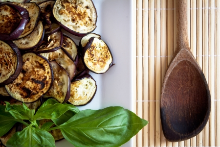 Platter of grilled aubergines with basil and wooden spoon on the side  photo