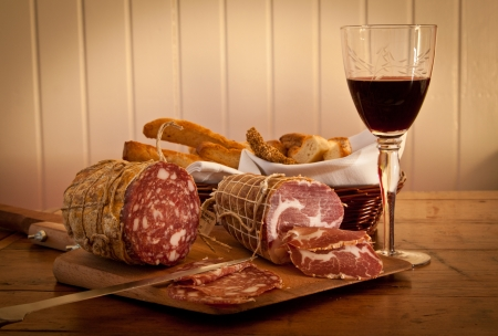 Delicious Mediterranean snack: red wine with salami and home-made bread.